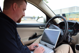 Officer Thompson inputs data from a vehicle inspection.